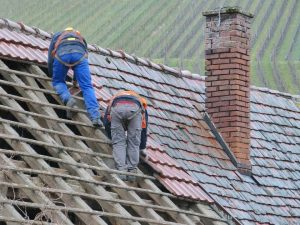 Two people working on roof repair