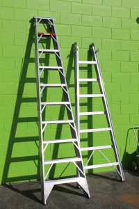 Ladders against a green wall
